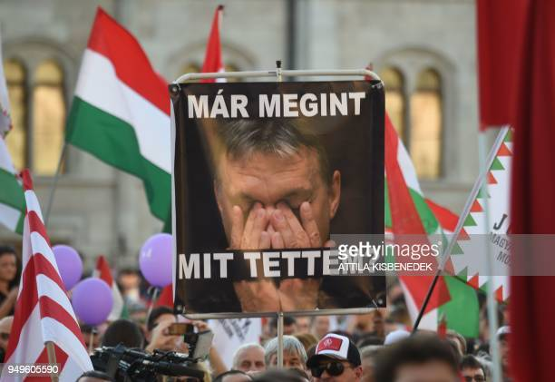 A protester holds a sign reading What have I done again and depicting Hungarian Prime Minister Viktor Orban while taking part in an antigovernment...