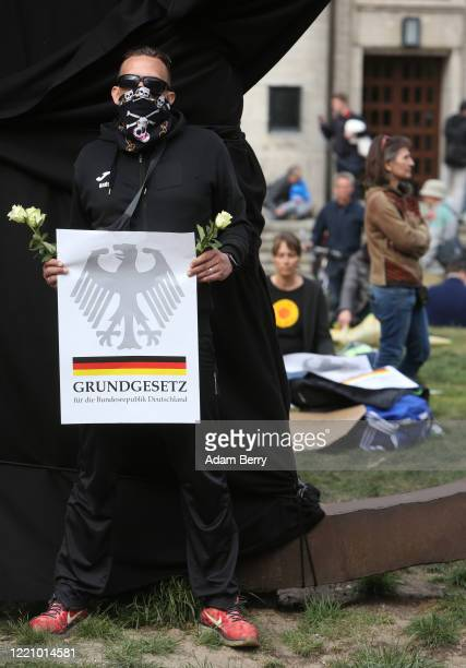 Protester holds a sign referring to the Grundgesetz, or German constitution known as the basic law, as he demonstrates against restrictions on public...