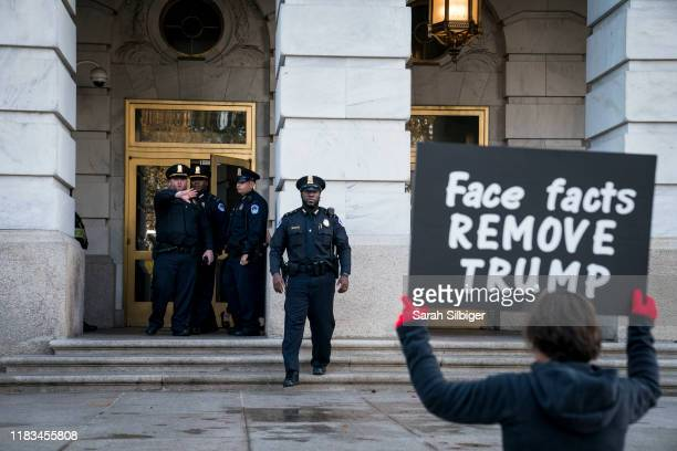 A protester holds a sign that reads Face facts remove Trump outside Longworth House Office Building during a recess between backtoback House...