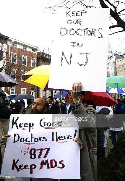 A protester holds a sign that reads 'Keep Our Docs In NJ' at a rally at the New Jersey Capitol Complex February 4 2003 in Trenton New Jersey About...