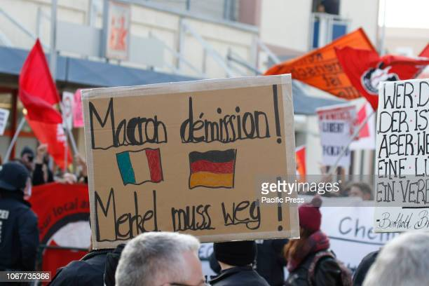 A protester holds a sign that reads 'Macron resignation Merkel has to go' Around 250 people from rightwing organisations protested in the city of...