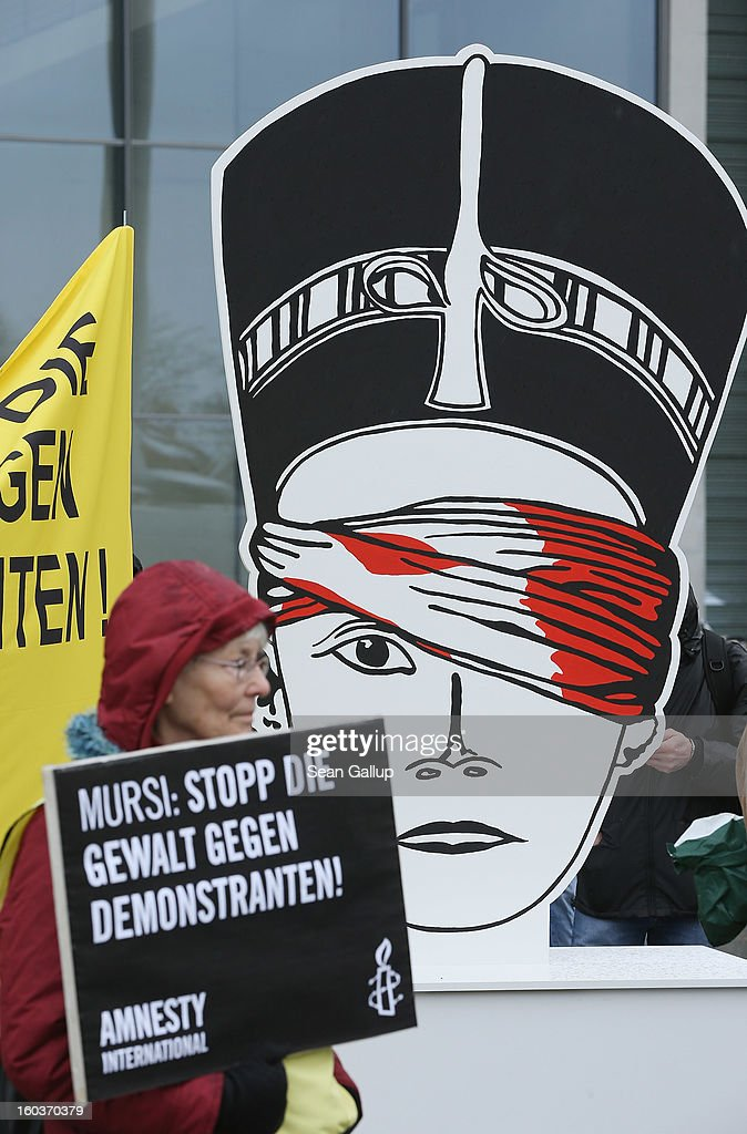 'Mursi: Stop The Violence Against Demostrators' next to a posterboard of a bandaged ancient Egyptian Queen Nefirtiti prior to the arrival of Egyptian President Mohamed Mursi at the Chancellery on January 30, 2013 in Berlin, Germany. Mursi has come to Berlin despite the ongoing violent protests in recent days in cities across Egypt that have left at least 50 people dead. Mursi is in Berlin to seek both political and financial support from Germany.
