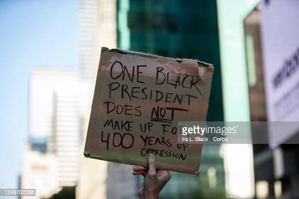 A protester holds a sign that reads One Black President does NOT Make Up for 400 Years Of Oppression as they march through the streets of New York...