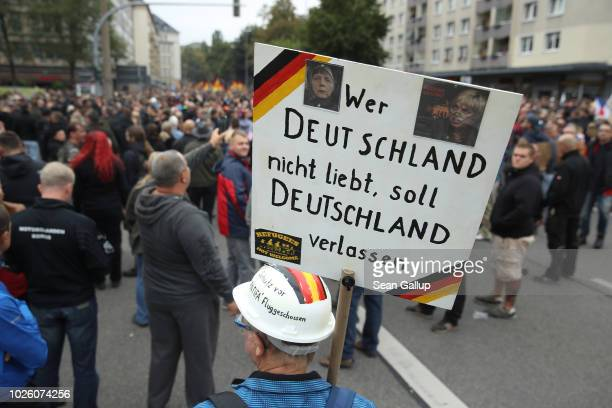 """Protester holds a sign that reads: """"Whoever doesn't love Germany should leave Germany"""" prior to a march of silence organized by the right-wing..."""