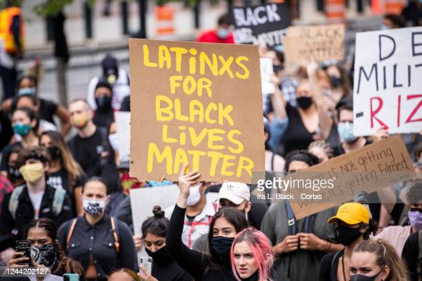 A protester holds a sign that says LATiNXS FOR BLACK LiVES MATTER among the large crowd in Foley Square Protesters took to the streets across America...