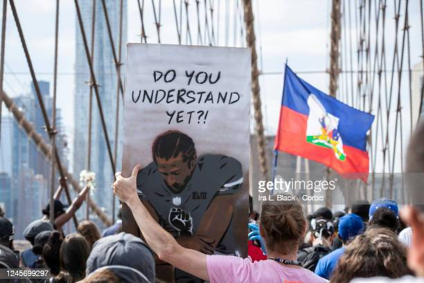 """Caucasian protester holds a sign that says,""""Do You Understand Yet?"""" with a picture of Colin Kaepernick, former quarterback for the San Francisco..."""