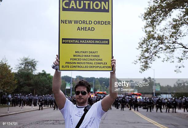 A protester holds a sign toward a crowd of students gathered behind riot police lines in the Oakland section September 24 2009 in Pittsburgh...