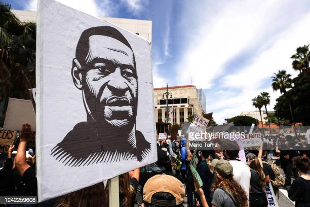 A protester holds a sign with an image of George Floyd during a peaceful demonstration over Floyd's death outside LAPD headquarters on June 2 2020 in...