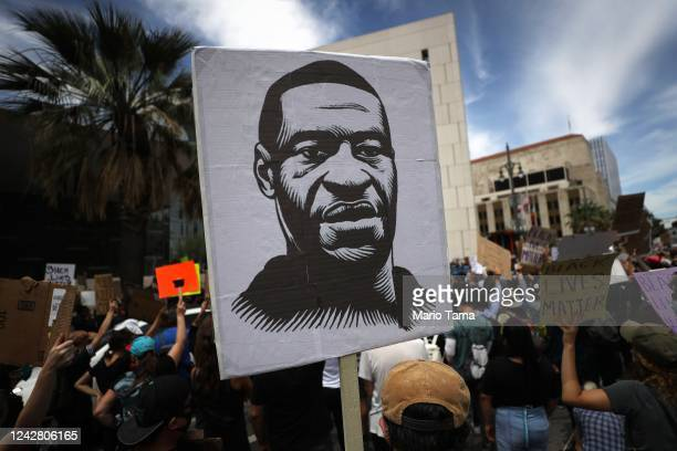 A protester holds a sign with an image of George Floyd during a peaceful demonstration over George Floyd's death outside LAPD headquarters on June 2...