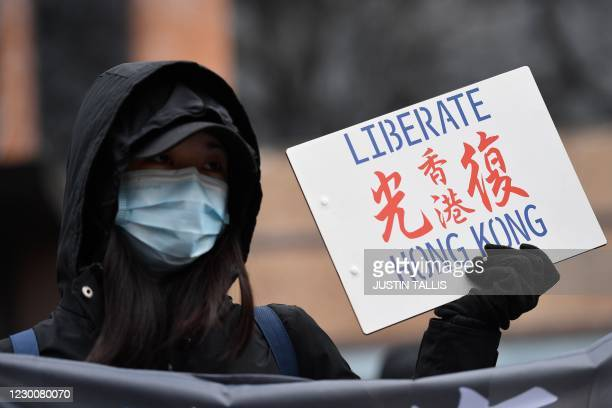 Protester holds a small placard at an event organised by Justitia Hong Kong to mourn the loss of Hong Kong's political freedoms, in Leicester Square,...