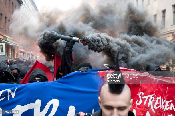 A protester holds a smoke bomb during the 'Revolutionary 1st May' demonstration in Oranienplatz in the Kreuzberg district on May 1 2017 in Berlin...