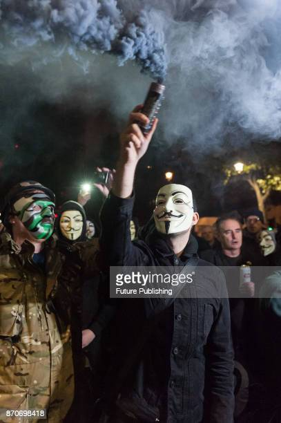 A protester holds a smoke bomb outside Downing Street as hundreds of demonstrators take part in the annual 'Million Mask March' organised since 2011...