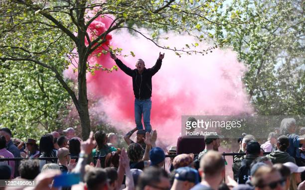 """Protester holds a smoke flare as he stands on a man's shoulders during a """"Unite For Freedom"""" anti-lockdown demonstration held to protest against the..."""