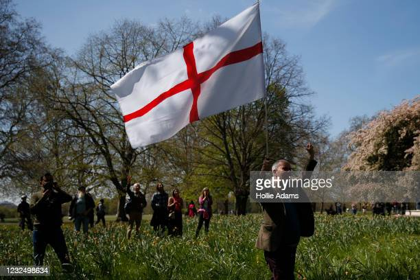 """Protester holds a St George's flag during a """"Unite For Freedom"""" anti-lockdown demonstration held to protest against the use of vaccine passports in..."""