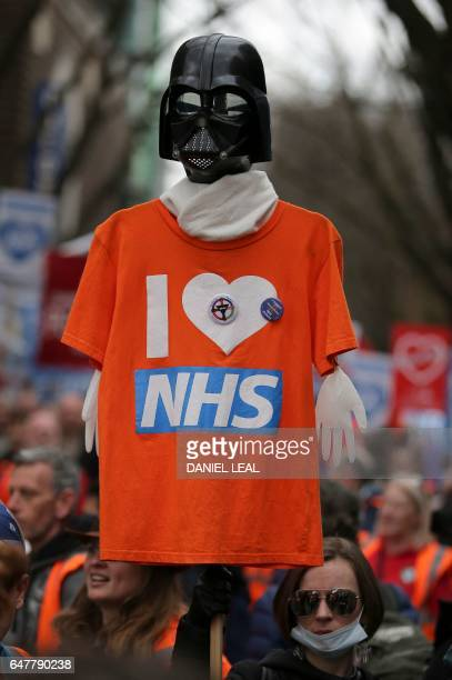 A protester holds a Star Wars themed TShirtplacard during a march against private companies' involvement in the National Health Service and social...