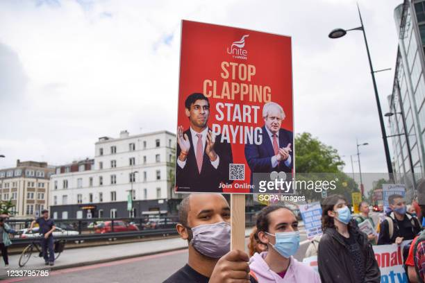 Protester holds a 'Stop Clapping, Start Paying' placard during the NHS workers demonstration outside University College Hospital. NHS workers and...