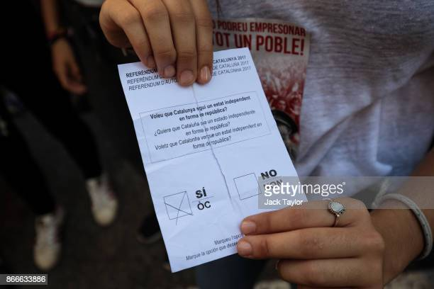 A protester holds a torn ballot paper marked 'si' for yes from the October 1st Catalan independence referendum during a proindependence strike of...