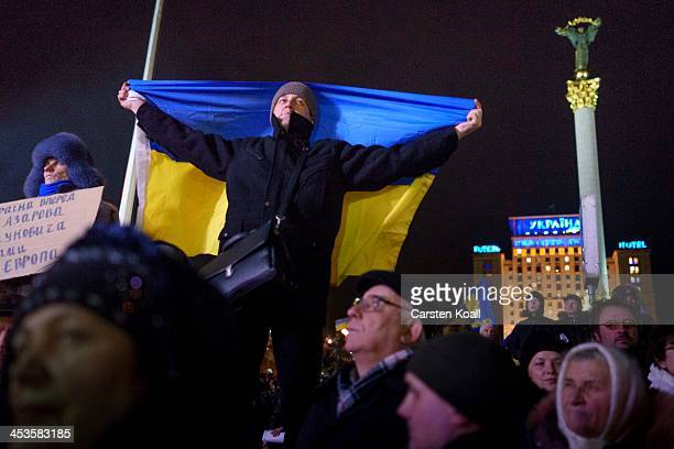 A protester holds a Ukrainian national flag as antigovernment protesters rally in Independence Square on December 4 2013 in Kiev Ukraine Thousands of...