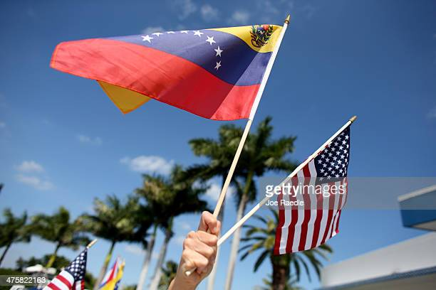 A protester holds a Venezuelan and American flag as she and other Venezuelans and their supporters show their support for the antigovernment protests...