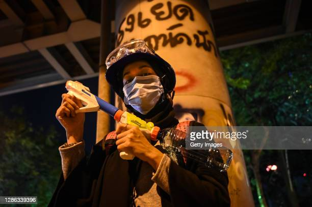 Protester holds a water pistol at the Ratchaprasong Intersection on November 18, 2020 in Bangkok, Thailand. Pro-democracy protesters amassed at a key...
