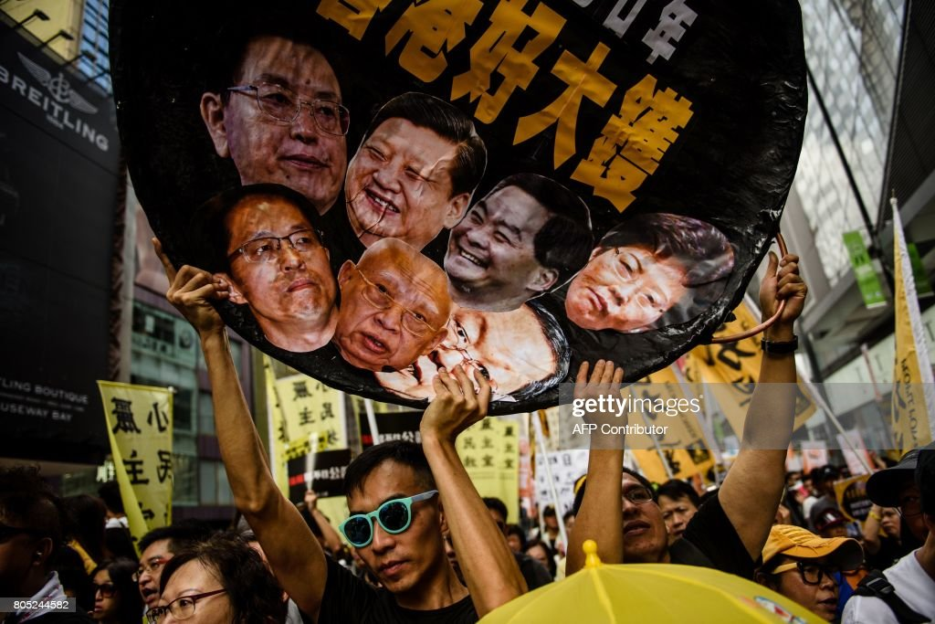 TOPSHOT - A protester holds a wok-shaped artwork with pictures showing the faces of (top row L-R) Chairman of the Standing Committee of the National People's Congress of China Zhang Dejiang, Chinese President Xi Jinping, former chief executive of Hong Kong Leung Chun-ying, new Chief Executive of Hong Kong Carrie Lam, (bottom row L-R) Director of the Liaison Office of the Central People's Government in Hong Kong Zhang Xiaoming, former Hong Kong chief executive Tung Chee-hwa and Director of the Hong Kong and Macau Affairs Office Wang Guangya during a protest march in Hong Kong on July 1, 2017, coinciding with the 20th anniversary of the city's handover from British to Chinese rule. China's President Xi Jinping warned July 1 that any challenge to Beijing's control over Hong Kong crossed a 'red line', as thousands calling for more democracy marched through the city 20 years since it was handed back by Britain. / AFP PHOTO / Anthony WALLACE