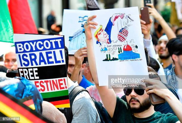 A protester holds acaricature depicting US President Donald Trump dropping a bomb with the lettering US Embassy on East Jerusalem while taking part...