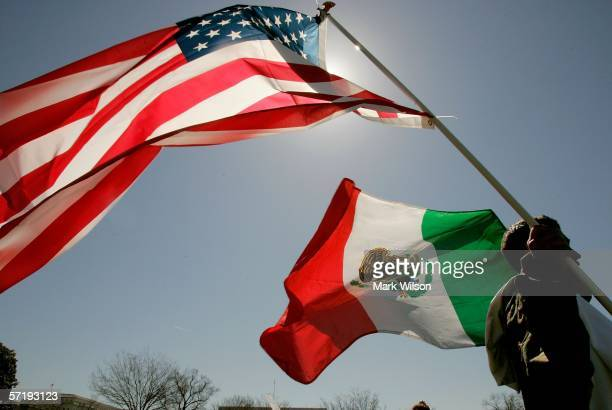A protester holds an American flag and a Mexican flag while participating in a protest on the west front of the US Capitol March 27 2006 in...