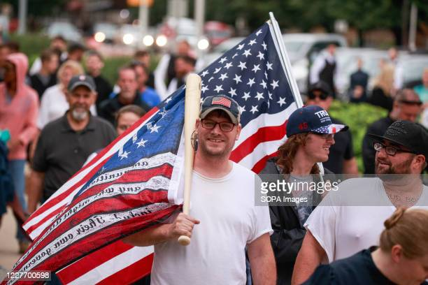 Protester holds an American flag attached to a cricket bat during the We Will Not Comply anti mask rally. People protest against both the...