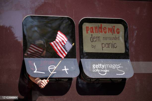Protester holds an American flag, with a message calling Democrats a pandemic, from a passing vehicle. Protesters gather outside Indiana Governor...