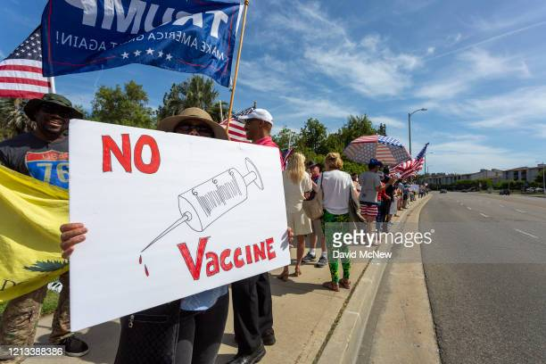 Protester holds an anti-vaccination sign as supporters of President Donald Trump rally to reopen California as the coronavirus pandemic continues to...