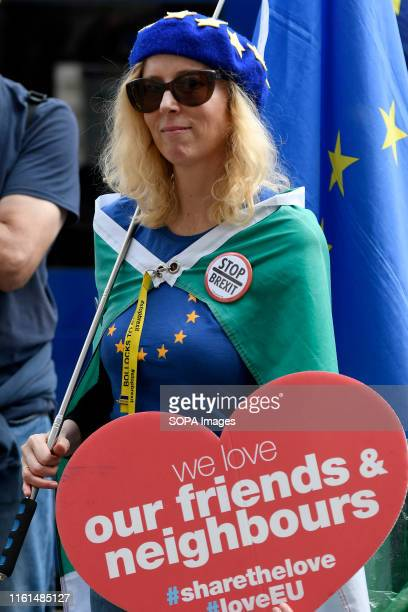 A protester holds an EU flag and a placards during the anti brexit protest Protesters gathered outside the Cabinet Office to demand for a revoke...