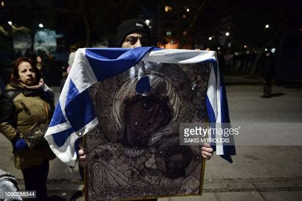 Protester holds an icon of the Virgin Mary drapped in the Greek flag as during a protest against an agreement to rename Greece's neighbour as the...