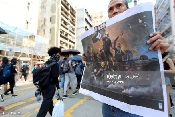 A protester holds an placard as people march past during a protest in the Sham Shui Po district in Hong Kong on October 1 as the city observes the...
