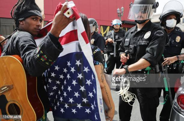 A protester holds and American flag upside down while standing off with police during a peaceful demonstration over George Floyd's death in Hollywood...
