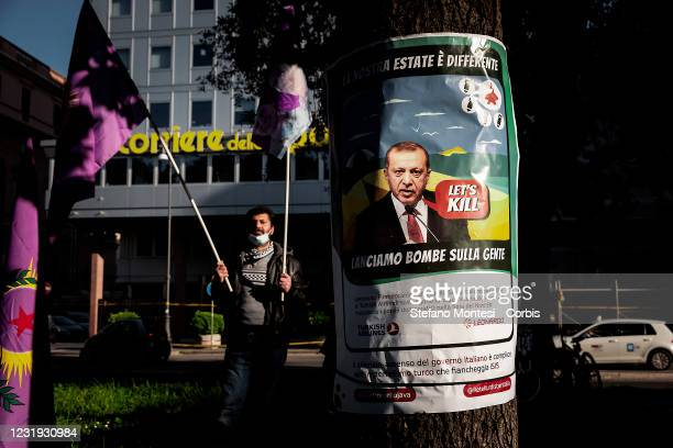 Protester holds flags during a demonstration of the feminist movement and the Kurdish people against Turkey's decision to withdraw from the Istanbul...