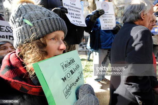 A protester holds her sign close to her face as Senator Ed Markey addresses a protest rally by government workers and concerned citizens against the...