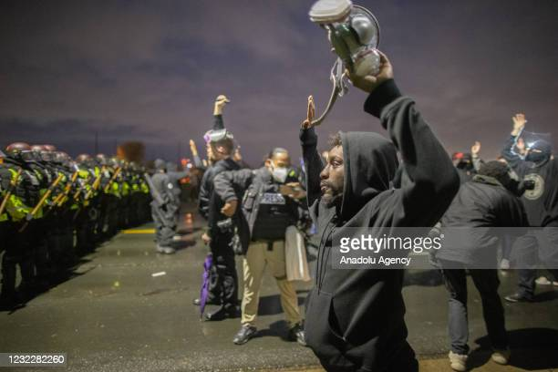 Protester holds his gas mask as he drops on his knees and raises his hands in the air in Brooklyn Center, Minnesota, U.S., on April 13, 2021.