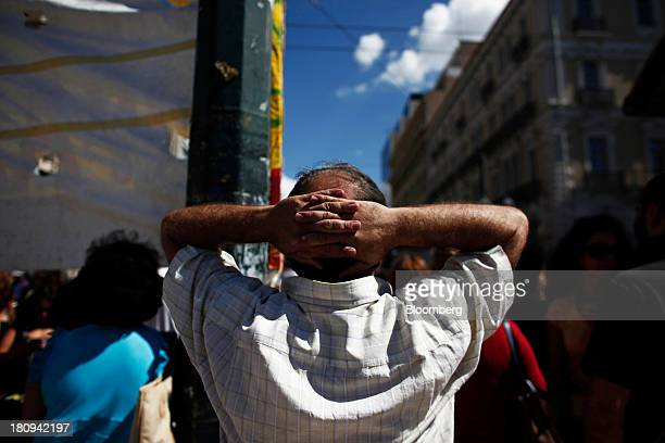 A protester holds his hands behind his head as he takes part in a demonstration to mark the start of a 48hour strike by Greece's biggest publicsector...