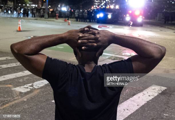 A protester holds his hands on his head in front of a formation of Detroit riot policeas protesters marched through the streets of Detroit Michigan...