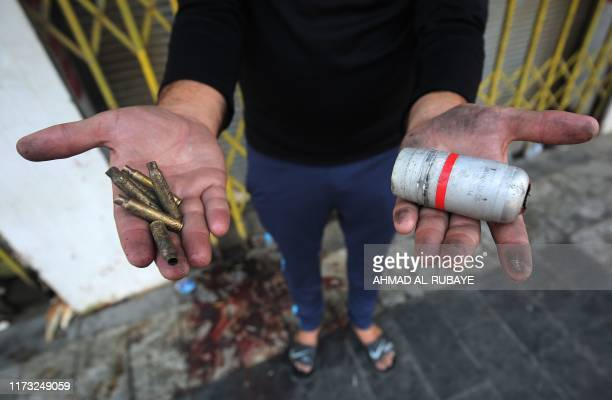 A protester holds in his hands the casings of live rounds and a spent tear gas canister reportedly fired by riot police during clashes amidst...