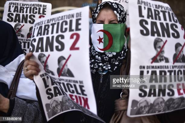 TOPSHOT A protester holds placards during a demonstration against ailing President Abdelaziz Bouteflika in the capital Algiers on March 29 2019...