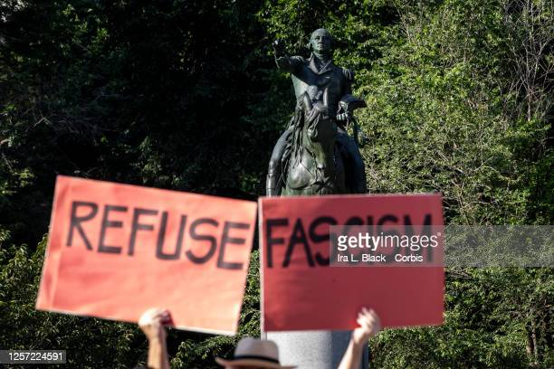 """July 18: A protester holds signs that say, """"Refuse Fascism"""" are held in front of the George Washington Statue in Union Square, New York. This was the..."""