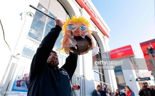 A protester holds the head of a Donald Trump pinata as people celebrate Joe Biden being elected President of the United States in the Castro district...