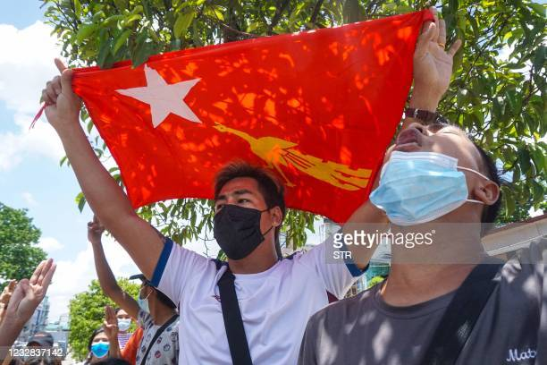 Protester holds the National League for Democracy flag during a demonstration against the military coup in Yangon on May 12, 2021.