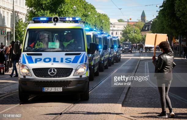 Protester holds the placard in front of police cars during a anti-racism demonstration on June 7, 2020 in Gothenburg, Sweden, in solidarity with...