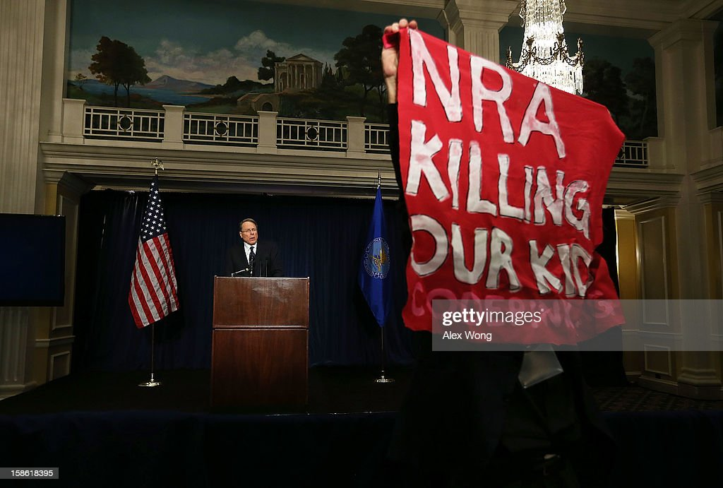 A protester holds up a bannaer as he protests during NRA CEO and Executive Vice President Wayne LaPierre's news conference at the Willard Hotel December 21, 2012 in Washington, DC. This is the first public appearance that leaders of the gun rights group have made since a 20-year-old man used a popular assault-style rifle to slaughter 20 school children and six adults at Sandy Hook Elementary School in Newtown, Connecticut, one week ago.