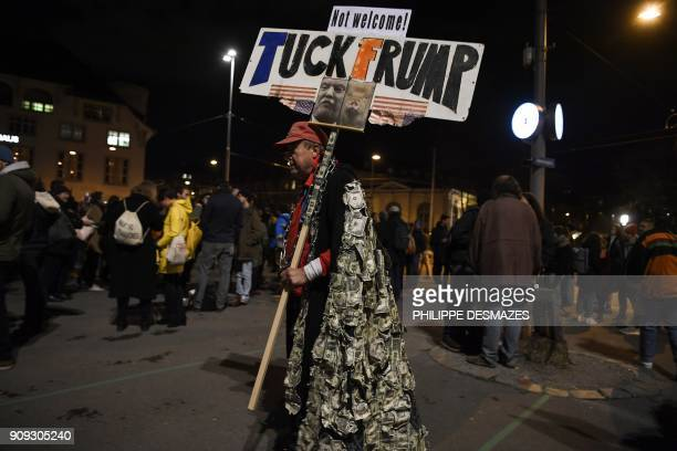 A protester holds up a banner during a protest against the attendance of the US president to the upcoming World Economic Forum in Davos on January 23...
