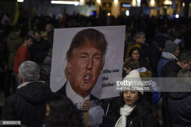 A protester holds up a banner with the image of the US president during a protest against his attendance to the upcoming World Economic Forum in...