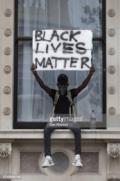 A protester holds up a 'Black Lives Matter' sign as they sit on a windowsill of the Foreign and Commonwealth Office during the Black Lives Matter...