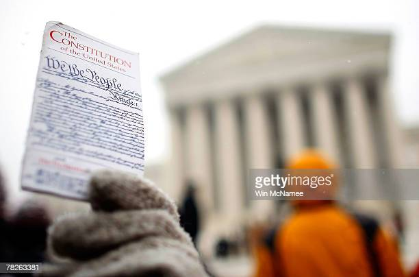 A protester holds up a copy of the US Constitution while demonstrating in front of the US Supreme Court December 5 2007 in Washington DC The Supreme...